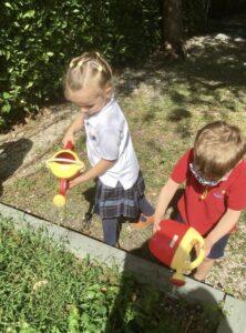 children watering a garden